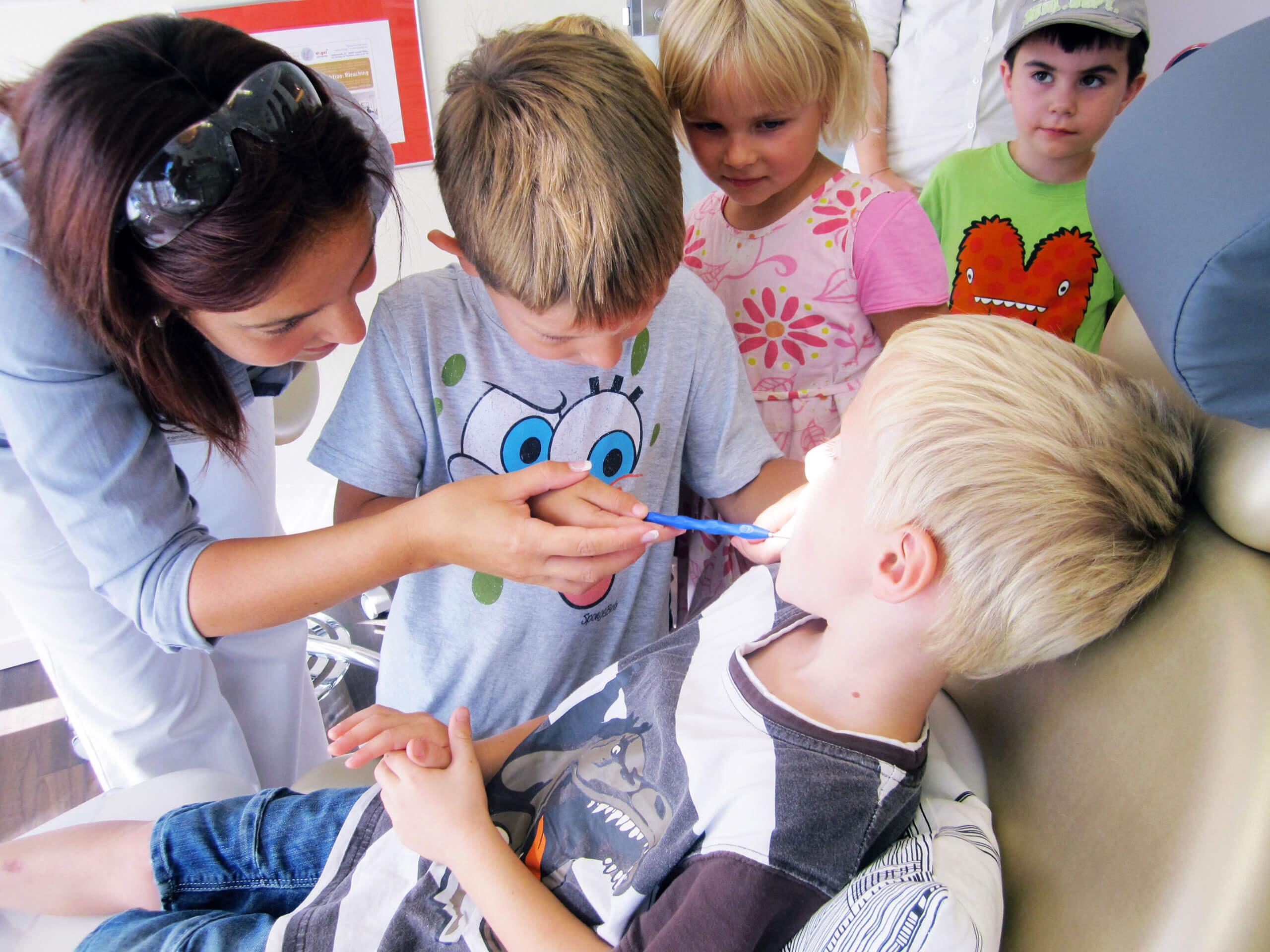 Vier Kinder im Kindergartenalter sind in einem Behandlungszimmer der Zahnarztpraxis Dr. Gal, eines der Kinder liegt auf dem Behandlungsstuhl, die Zahnärztin schaut mit einem Mundspielgel in seinen Mund