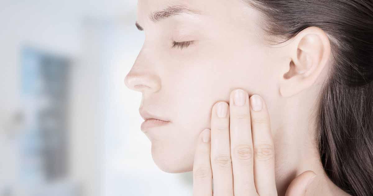 Seitliches Profil einer Jungen Frau, die eine Zahnfleischentzündung hat und mit der linken Hand ihre Backe festhält