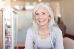 Ältere Dame, Ende 60, lächelt und denkt über neue Zähne nach
