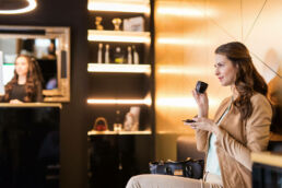 Frau sitzt im Prophylaxis Studio und führt eine Espressotasse an den Mund