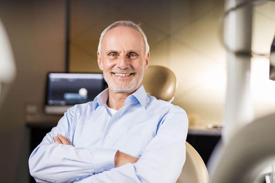 Lächelnder Mannes, der so um die 60 Jahre alt ist sitzt im Zahnarztstuhl und hat die Arme verschränkt