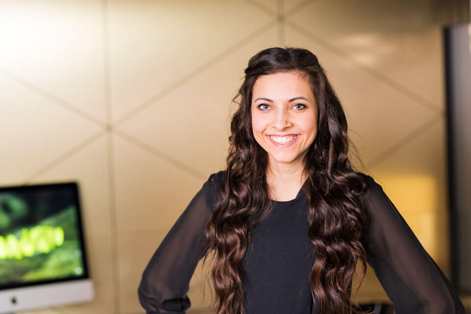 Lächelde junge Frau mit langen braunen Haren und schwarzer Kleidung