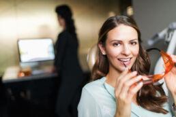 Im Vordergrung eine junge lächelnde Frau im Behandlungsraum der Zahnarztpraxis Dr. Gal mit Schutzbrille in den Händen, im Hintergrund eine Helferin