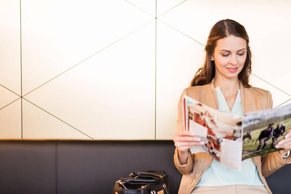 Frau sitzt auf Sofa im Wartezimmer der Zahnarztpraxis Dr. Gal und liest eine Zeitschrift