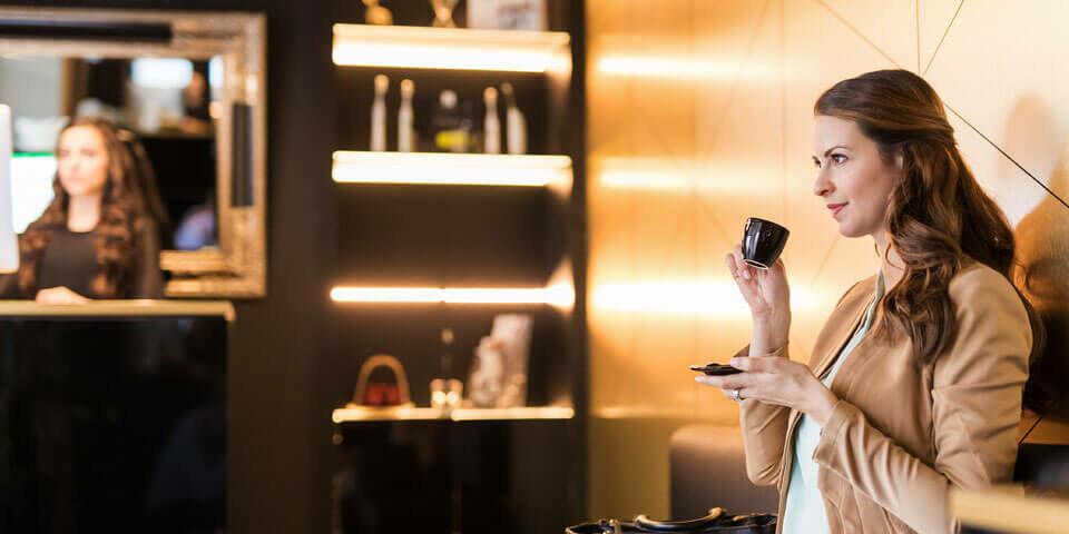 Frau sitzt im Wartebereich und führt eine Espressotasse an den Mund
