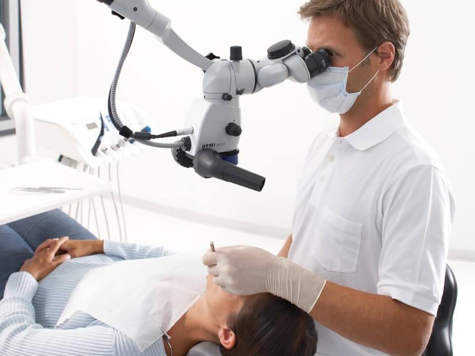 Frau liegt auf einem Zahnarztstuhl, der Zahnarzt schaut durch ein Mikroskop über dem gesicht der Frau auf ihre Zähne