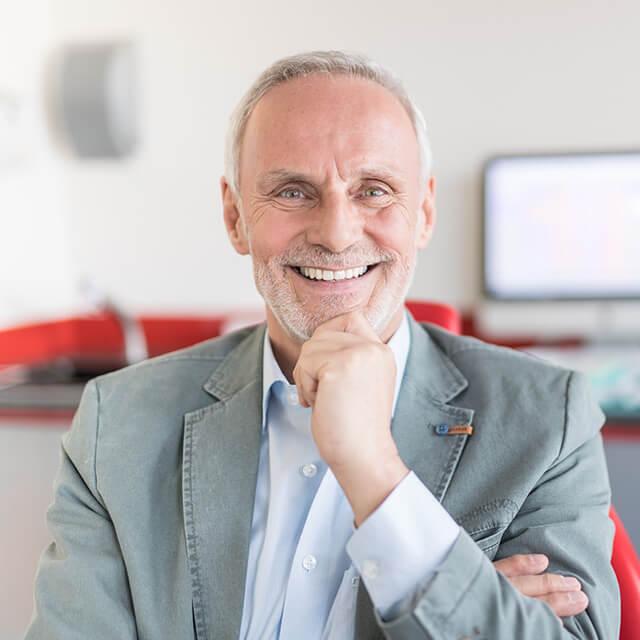 Mann, in den 60ern, sitzt auf einem rotem Stuhl und lächelt, mit seiner linken Hand hält er sein Kinn fest