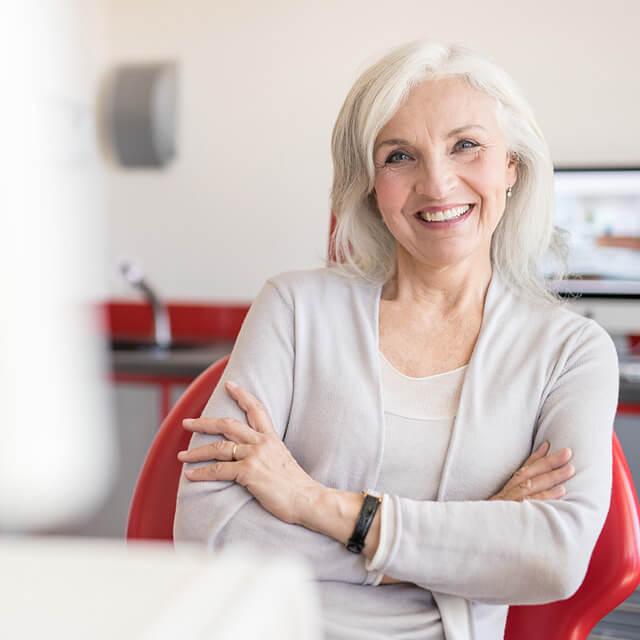 Frau, Ende 60, sitzt in einem roten Stuhl und hat ihre Arme verschränkt
