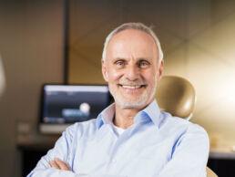 Lächelnder Mannes, der so um die 60 Jahre alt ist sitzt im Zahnarztstuhl