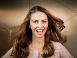 Gesicht in Grossaufnahme einer lächelnden junge Frau mit langen braunen Haaren