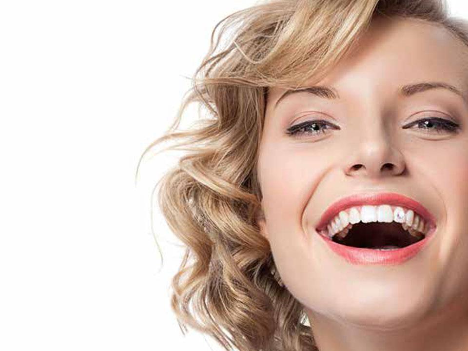 Gesicht einer jungen lachenden Frau im Grossformat, an einem Schneidezahn befindet sich ein Swarovskistein
