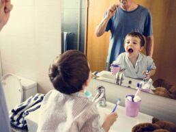 Vater und kleiner Sohn stehen beide im Bad, Vater putzt Zähne Sohn schaut in den Spiegel, hat den Mund aufgerissen und prüft, ob das Zähneputzen als Kind erfolgreich war