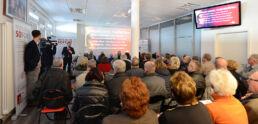 Konferenzraum gefüllt mit Stuhlreihen und Peronen, die einem Vortrag folgen, vorne steht neben der Leinwand der Moderator