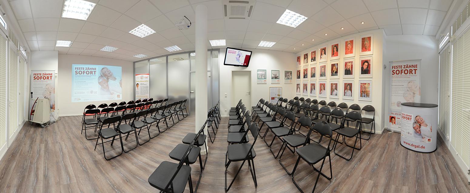 Raum mit Stuhlreihen ausgestattet, vorne eine Leinwand, hinten an der Wand hängen Fotos von den den Mitarbeitern der Zahnarztpraxis Dr. Gal