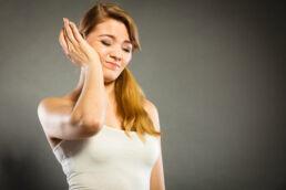 schmerzverzehrtem Gesicht, weil ein Zahn wackelt, hält ihre rechte Hand an die rechte Backe