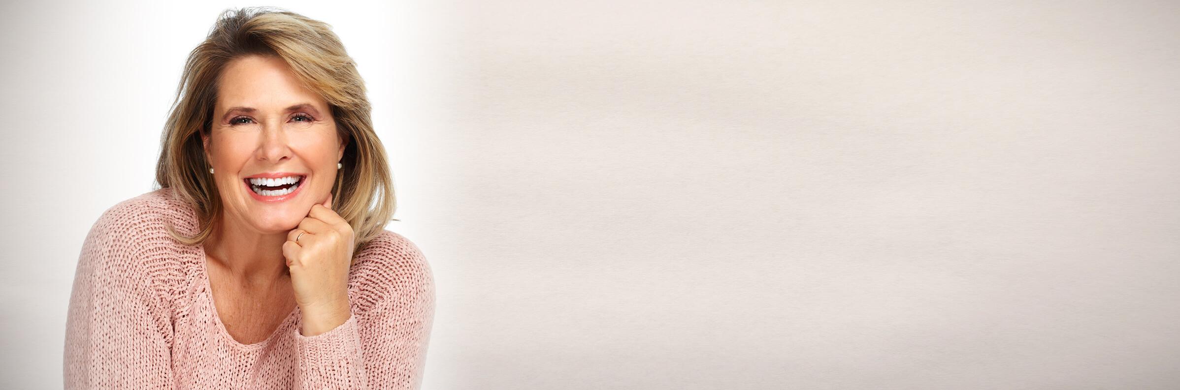 Gesicht und Oberkörper einer lachenden Frau mittleren Alters, die sich über ihre neuen feste Zähne freut, sie trägt einen rosa Wollpulli, der Hindergrund ist hellgrau