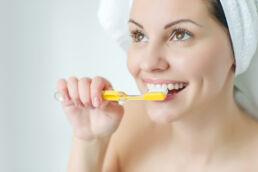 Das Gesicht einer jungen Frau in Grossaufnahme, die sich die Zähne putzt, Haare sind verdeckt durch einen Handtuchturban, der Hindergrund ist weiss gehalten