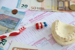 Zu sehen sind Auszüge eines Heil- und Kostenplans, Auszüge einer Zahnzusatzversicherung, eine Zahnbürste, Euro Geldscheine und Münzen, ein Gebiss aus Gips