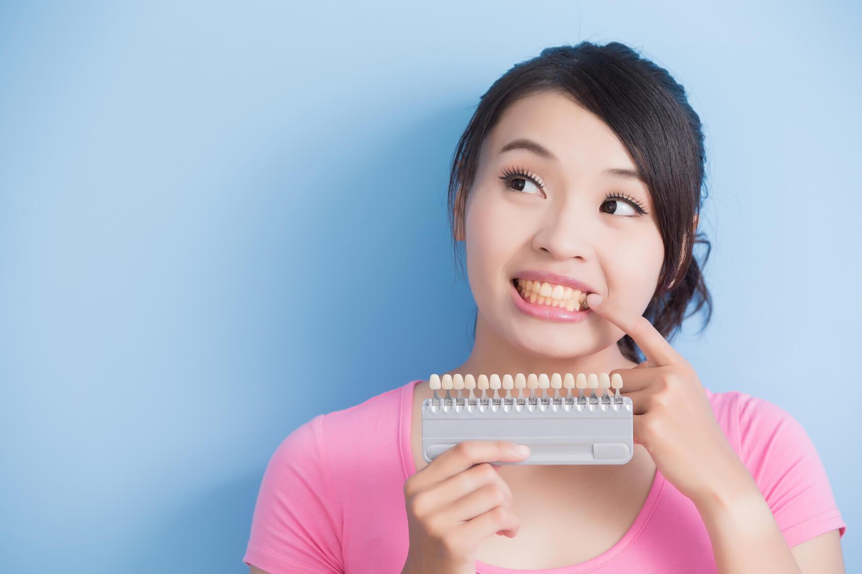 Junge asiatische Frau mit rosa T-Shirt steht vor blauem Hintergrung, hält in der linken Hand Zahnmuster, da sie ihre Zähne bleichen möchte, mit der rechten Hand zeigt sie auf ihre Zähne