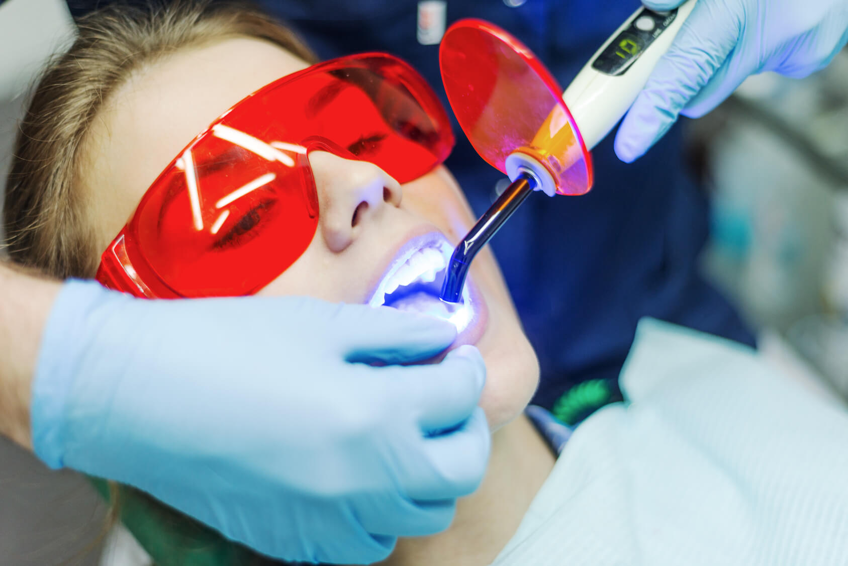 Frau liegt auf Zahnarztstuhl, hat eine rote Brille an und die Hände des Zahnarztes führen einen Dental-Laser in den Mund
