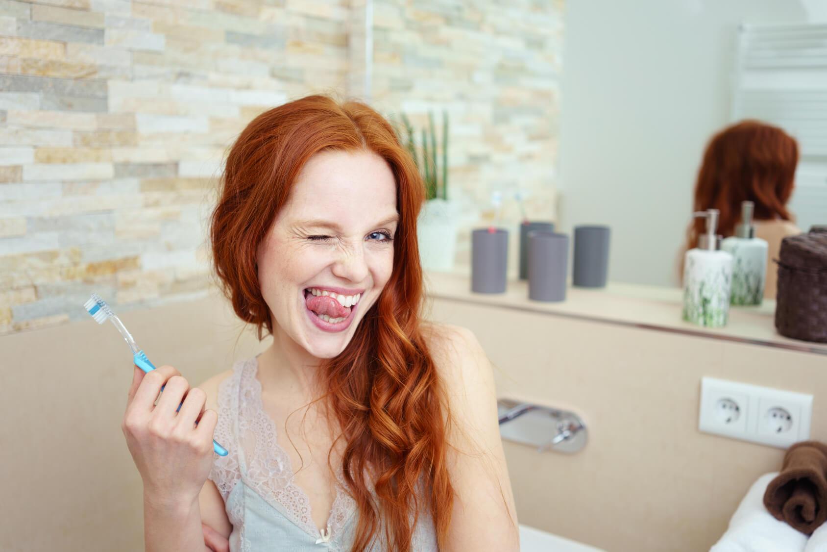Junge Frau mit langen roten Haaren und Zahnkrankheiten steht im Bad und knipst ein Auge zu und hält die Zunge an die Zähne, im Hintergrund ist ein Spiegel