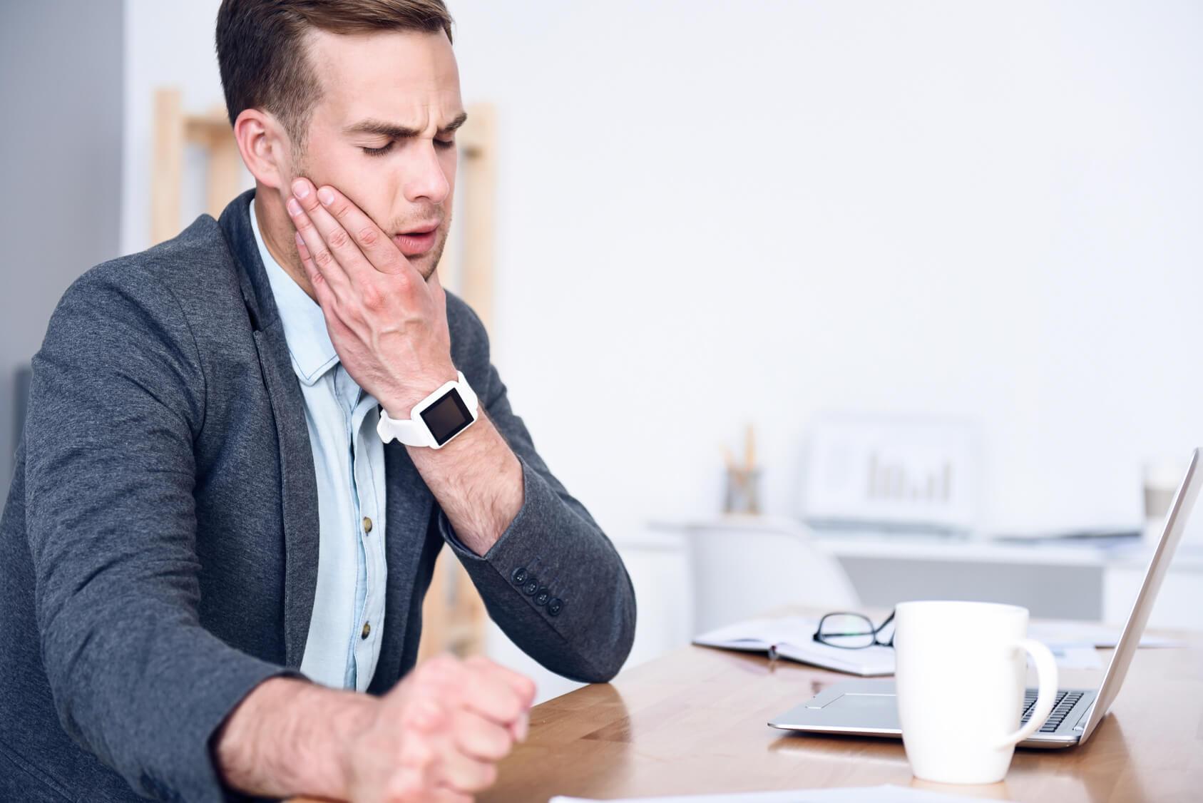 Junger Mann sitzt am Schreibtisch vor einem Laptop, zur rechten eine weisse Kaffeetasse, mit seiner linken Hand hält er seine linke Backe fest, da er Zahnschmerzen hat
