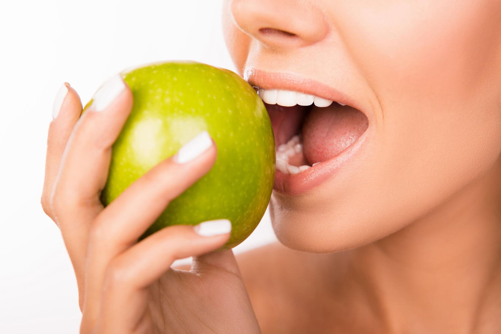 Großaufnahme eines Mundes einer jungen Frau, die in der rechten Hand einen grünen Apfel hält, zum ersten Biss ansetzt und dabei über zahngesunde Ernährung nachdenkt