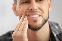 Großaufnahme Gesicht eines jungen Mannes, der mit seiner rechten Hand die rechte Wange festhält und vor Schmerzen sein Gesicht verzieht, weil seine Zähne wackeln
