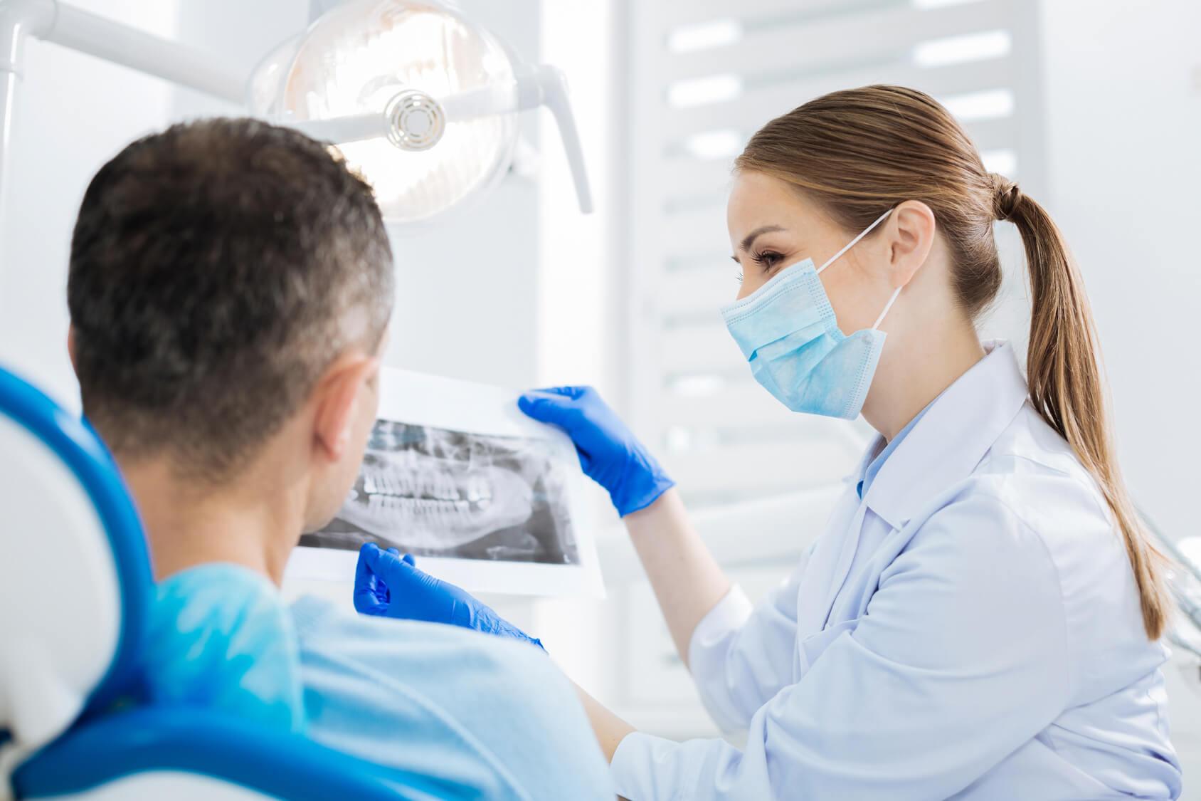 Zahnärztin mit Mundschutz zeigt dem Patienten auf Zahnarztstuhl sein Röntgenbild und erklärt die Innovationen der Zahnmedizin