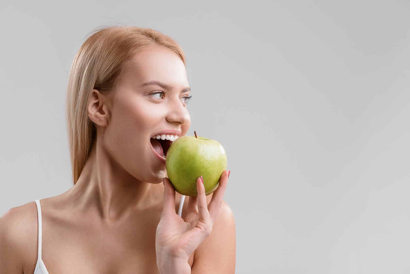 Junge Frau hält grünen Apfel in der Hand, sie freut sich, dass sie keine losen Zähne hat und und setzt zum ersten Biss an