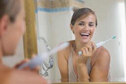Junge lächelde Frau steht im Bad vorm Spiegel, hält in der linken Hand eine elektrische Zahnbürste und denkt über die Möglichkeiten der smarten Zahnpflege nach