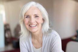 Ältere Dame, Ende 60, lächelt und denkt über schöne Zähne nach