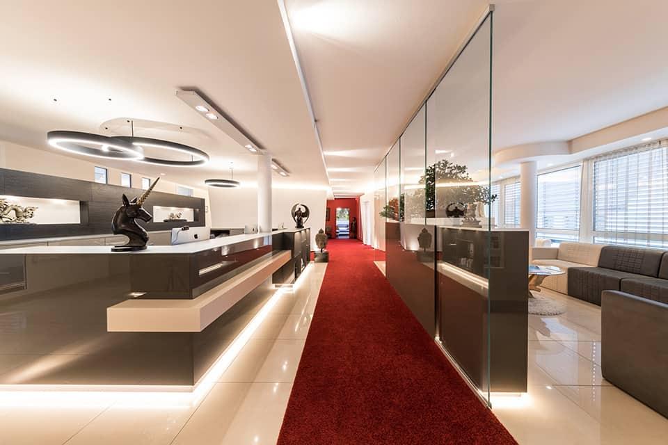 Auf der linke Seite des Bildes ist der Empfangsbereich mit grauer Theke und rotem Teppich zu sehen, auf der rechten Seite ein Wartebereich mit beige grauen Sofas und einem Couchtisch aus Glas