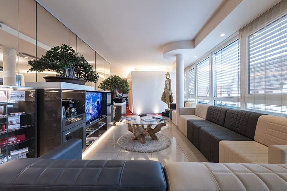 Warteraum mit beige grauen Sofas auf der rechten Siete des Bildes und einem grauen Sideboard auf der linken Seite