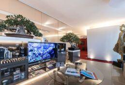 Ausschnitt des Wartebereiches mit Großaufnahme des Sideboards, darauf stehend ein Fernseher, integriert eine Kaffebar mit verschiedenen Nespressokapseln