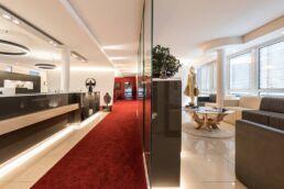 Auf der linke Seite des Bildes ist der Empfangsbereich mit grauer Theke und rotem Teppich zu sehen, auf der rechten Seite ein Wartebereich mit beige braunen Sofas und einem Couchtisch aus Glas