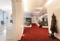 Auf der rechten Seite des Bildes ist der Eingangsbereich der Praxis mit Empfangstheke, rotem Teppich und verschiedenen asiatischen Skulpturen, auf der lienken Seite ist ein Besprechungsraum mit weissen Möbeln und Tisch zu sehen