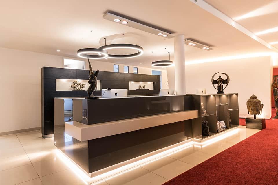 Empfangstheke in grau gehalten mit modernen Lampen an der Decke und rotem Teppich vor der Theke