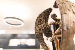 Sitzender Mann mit Engelsflügeln als goldene Skulptur