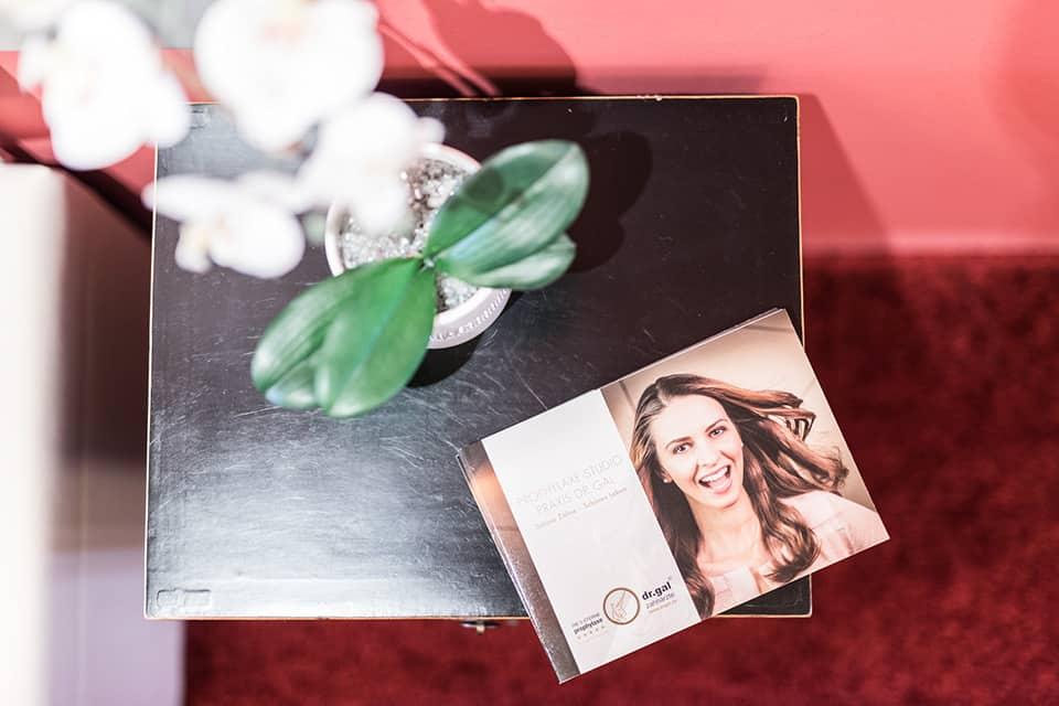 Flyer für Zahnarztpraxis Dr. Gal liegt auf kleinem Holzschränkchen mit Pflanze
