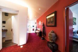 Auf der rechten Seite befindet sich eine rote Wand mit Dr. Gal Logo draufgedruckt, davor eine weisse Bank, links und rechts davon ein asiatisches Holzschränkchen und jeweils eine asiatische Skulptur. Links ist eine offene Tür in einen Raum zu sehen