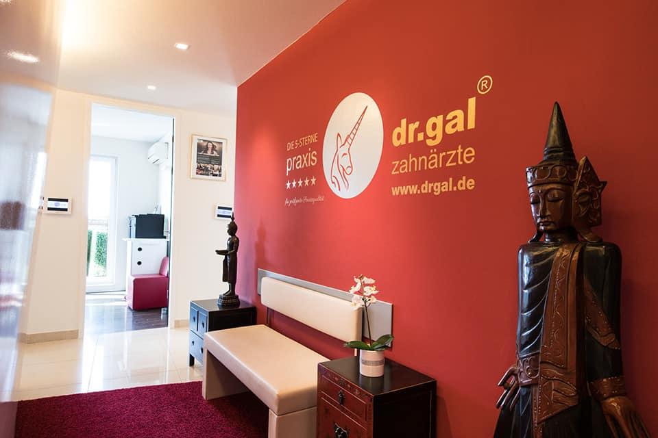 Rote Wand mit Dr. Gal Logo draufgedruckt, davor eine weisse Bank, links und rechts davon ein asiatisches Holzschränkchen und jeweils eine asiatische Skulptur