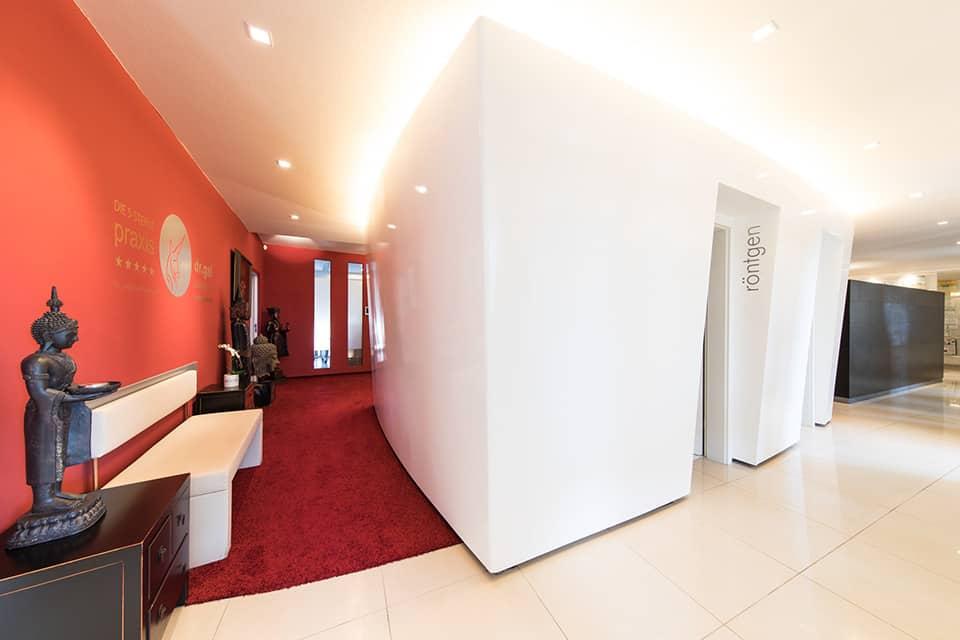Eingang zum Röntgenraum rechts im Bild zu sehen, link ist ein Durchgang, ausgelegt mit rotem Teppich und roter Wand. Möbeliert ist der Durchgang mit einer weissen Bank und asiatischen Schränkchen und mehreren asiatischen Skulpturen.
