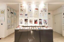 graues Sideboard mit vielen Informationsbroschüren, drum herum an der Wand hängend viele Auszeichnungen