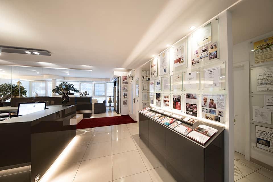 Eingangsbereich mit vielen Auszeichnungen an der rechten Wand und einem Board mit Infoflyern, links die graue Theke