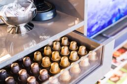 Kaffestation mit sorgfältig aufgereihten Nespresso Kapseln in Metallicfarben, die in einer Schublade liegen