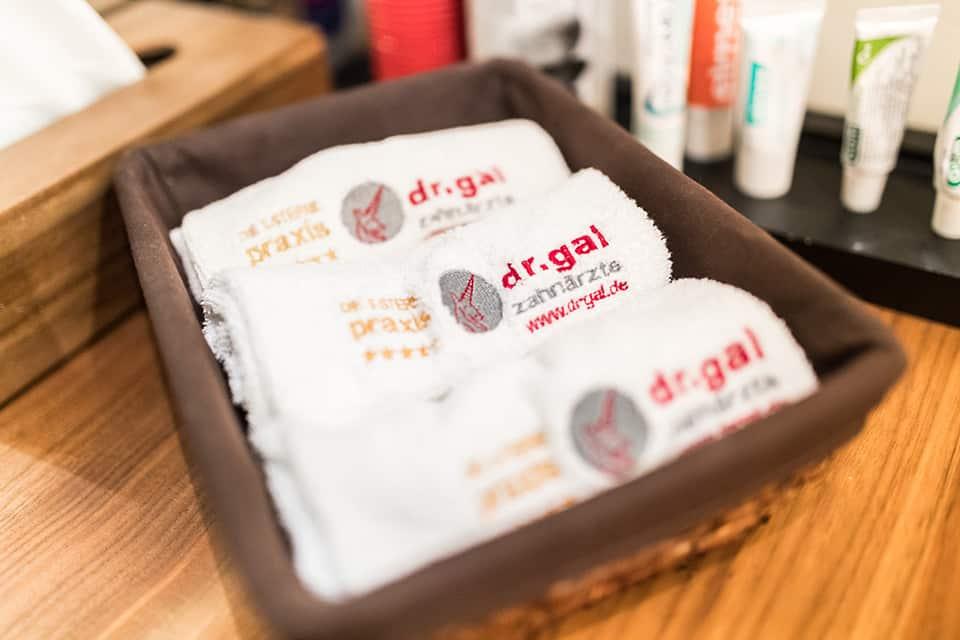In einem braunen Körbchen liegen zusammengerollt drei kleine Handtücher mit Dr. Gal Logo