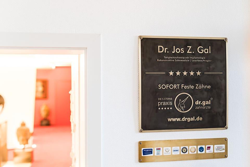 Es hängen Auszeichnungen and der Wand,  besonders hervorgehoben ist die Schild von Zahnarzt  Dr. Jos Gal