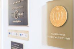 Es hängen Auszeichnungen and der Wand, besonders hervorgehoben ist die Auszeichnung World Member of Leading Implantat Centers
