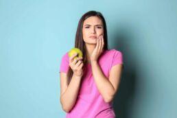 Junge Frau mit rosa T-Shirt und langen braunen Haaren hält in der rechten Hand einen grünen Apfel und sie hat das Gefühl, dass beim nächsten Biss die Zähne brechen könnten